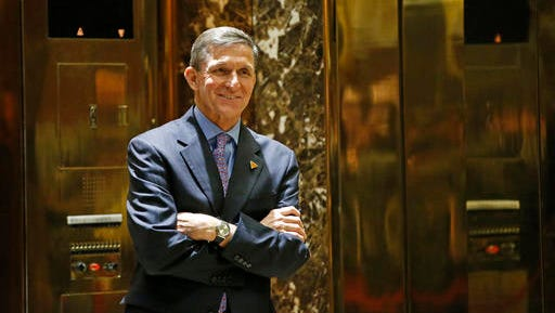FILE - In this Dec. 12, 2016 file photo, National Security Adviser-designate Michael T. Flynn waits for an elevator in the lobby at Trump Tower in New York. The Obama administration is aware of frequent contacts between President-elect Donald Trump's top national security adviser Michael Flynn and Russia's ambassador to the United States, including on the day President Barack Obama hit Moscow with sanctions in retaliation for election-related hacking, a senior U.S. official said Friday, Jan. 13, 2017.