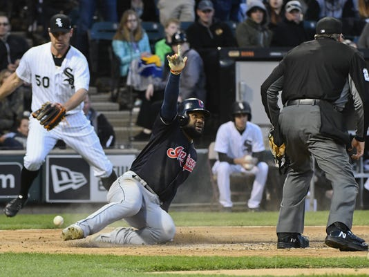 Cleveland Indians' Abraham Almonte, center, points while watching umpire Jerry Layne, right, for the call after he scores as Chicago White Sox starting pitcher Mike Pelfrey (50) looks on during the fifth inning of a baseball game in Chicago on Saturday, April 22, 2017. (AP Photo/Matt Marton)