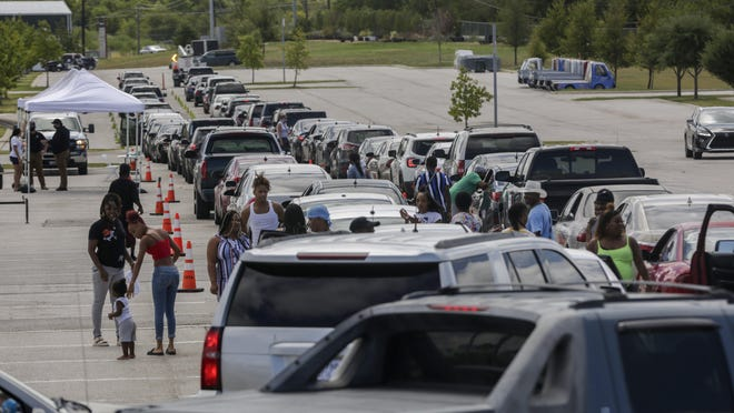 Hundreds of Hurricane Laura evacuees wait in their cars as they line up for hotel vouchers at the Circuit of the Americas in Austin on Aug. 26.