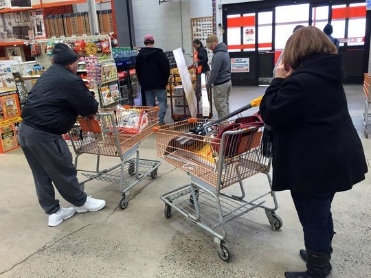 Shoppers at the Piscataway Lowe's look over shovels and ice melt on Wednesday as a winter storm approaches.