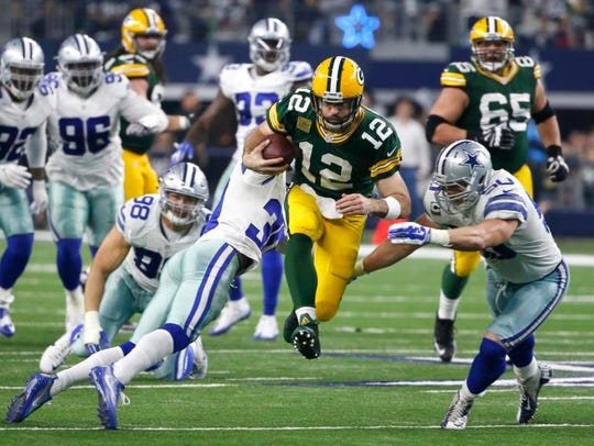 Packers quarterback Aaron Rodgers (12) tries to elude