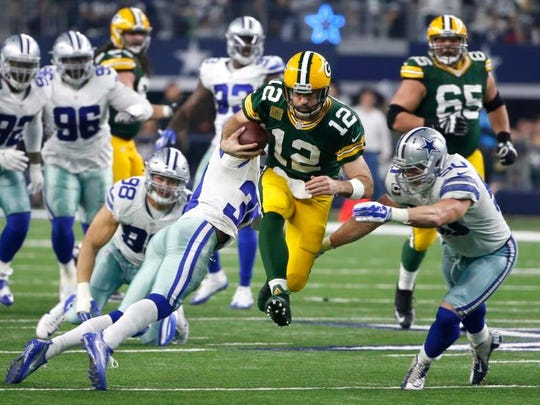 Packers quarterback Aaron Rodgers (12) tries to elude Cowboys' Sean Lee (50) and Anthony Brown (30) during Sunday's NFC Divisional matchup.