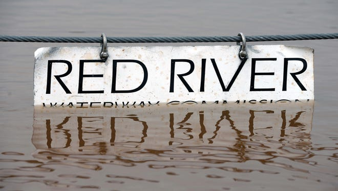 A sign for the Red River is partially submerged at the  Arthur Tesague multi-use trail and boat launch as waters from the river forced several boat launches and parks to be closed.