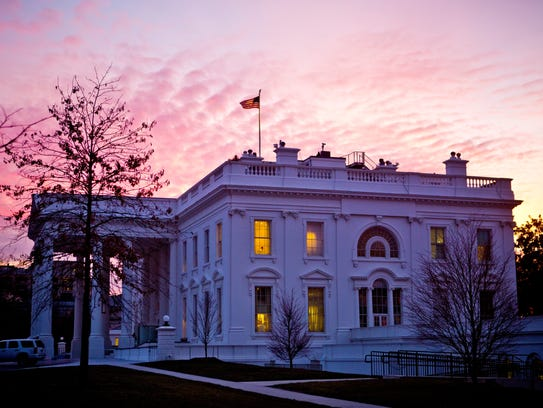 Morning sunlight lights up the sky over the White House