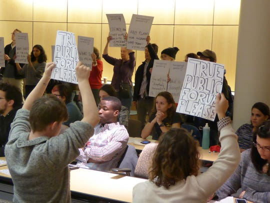 Protesters hold up signs Wednesday calling for a 'true