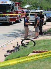 Abilene Police Department personnel talk with a potential witness near the bike a man shot Friday at the corner of South Third and Larkin streets was riding.