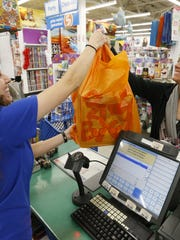 Cashier Samra Vatres hands Jessica Danilson of Cedar Rapids her purchases on Black Friday in 2015.