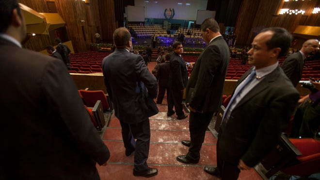 Security guards surround the area where two women threw flour into the face of Guatemalan Vice President Roxana Baldetti when she was leaving the National Theatre in Guatemala City, Tuesday.