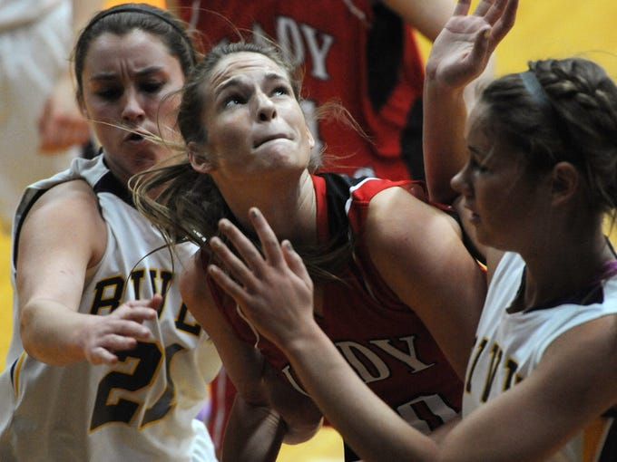 Borden's Abby Ellis (center) is trapped in the defense of Vincennes Rivet's Kelsey Ivers (left) and Bailey Niehaus (right) as she tries to go up for a basket on Saturday at West Washington High School. Feb.22, 2014