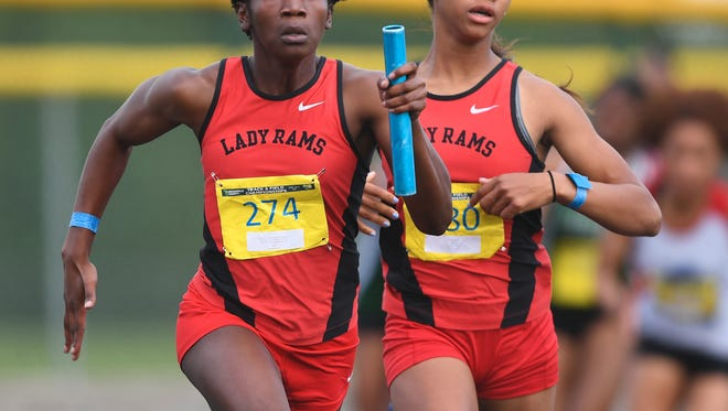 Hillcrest's Zariere Dumas, left, runs the final leg of the 4x100 meter relay after taking the baton from teammate Zahria Jones during the Greenville County track meet at Eastside High on Thursday.