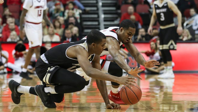 U of L's V.J. King, right, dives for a loose ball with Bryant's Ikenna Ndugba during the first half of play against the visiting Bryant Bulldogs at the KFC Yum! Center on Monday night. Dec. 11, 2017