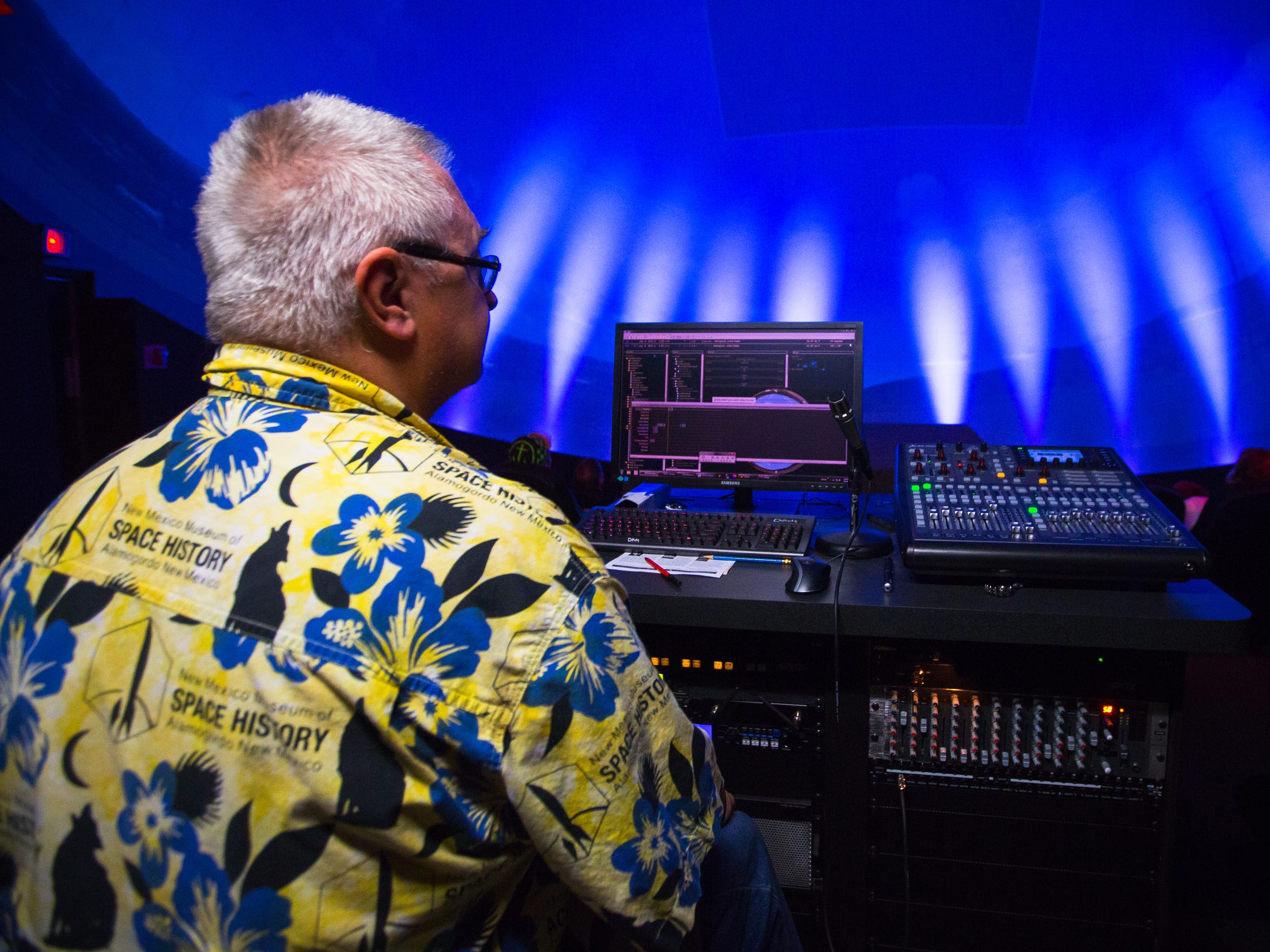 New Mexico Museum of Space History Science Specialist Paul Hughen sits at a control console in the New Horizons Dome Theater & Planetarium before the start of a show, July 8, 2016.