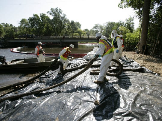 Workers pull oil-soaked absorbing booms from the Kalamazoo