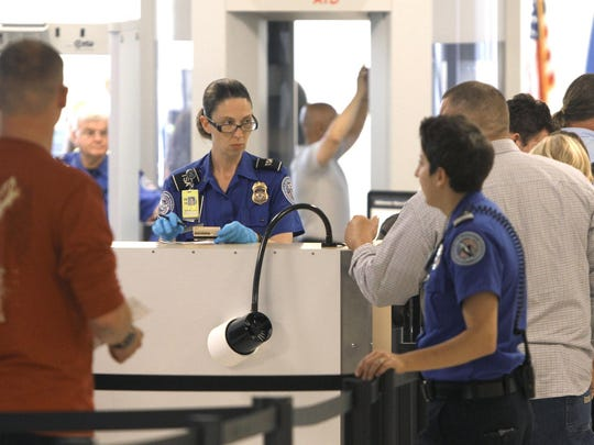 TSA agents instruct fliers and check identification