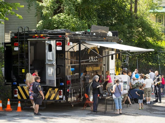 Ithaca police officers and and members of the public mix around the department's SWAT and Mobile Command vehicle Saturday morning at the department's open house.