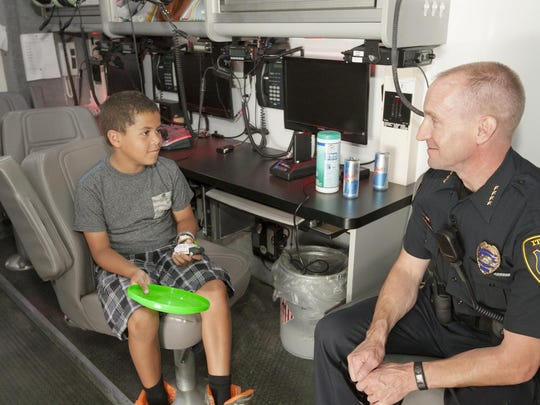 Eight-year-old Tristan Butler of Ithaca talks with Ithaca Police Chief John Barber Saturday morning inside the department's SWAT and Mobile Command vehicle. The IPD held an open house to meet the community Saturday morning.