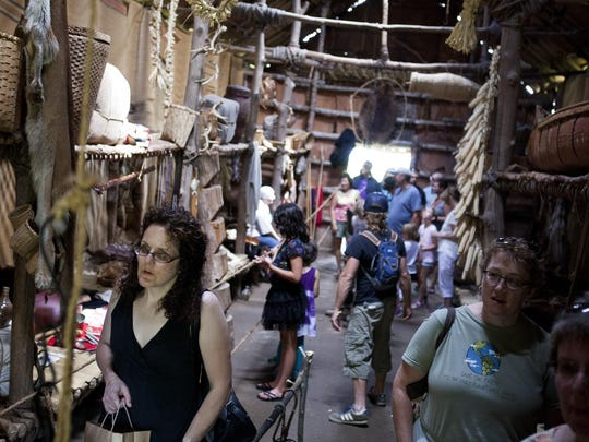 Visitors walk through a longhouse at Ganondagan's Dance and Music Festival in Victor on Saturday, July 26, 2014.