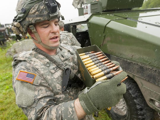 First Lt. Patrick Cassidy of Syracuse explains the ammunition used in a .50 caliber machine gun. Each box hold 100 rounds, every fifth round is a tracer round that lights up in red, visible even in daylight.
