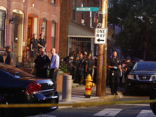 Crowds and Wilmington police gather outside a home at the corner of Washington and Fourth streets where a person was murdered July 23, 2015.
