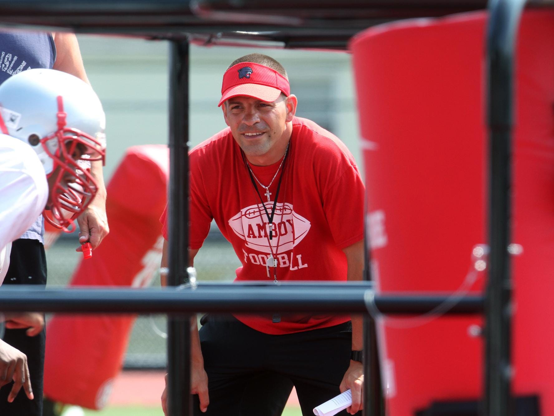 Perth Amboy first year football coach Brad Bishop works with his players during preseason practice, Wednesday, August 20, 2014, in Perth Amboy, NJ. Photo by Jason Towlen