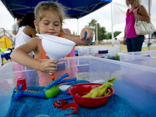 Megan Theurer, 3, of Weston plays in a sensory box