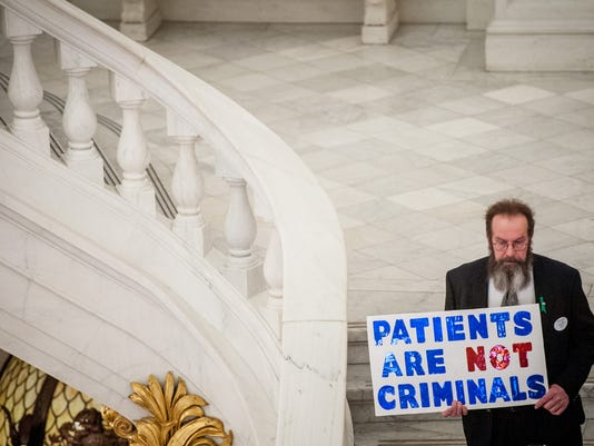 A demonstrator holds a sign in support of medical marijuana during a cannabis reform rally at the Capitol rotunda in Harrisburg on Monday, March 31, 2014. Jeff Lautenberger -- For the Evening Sun