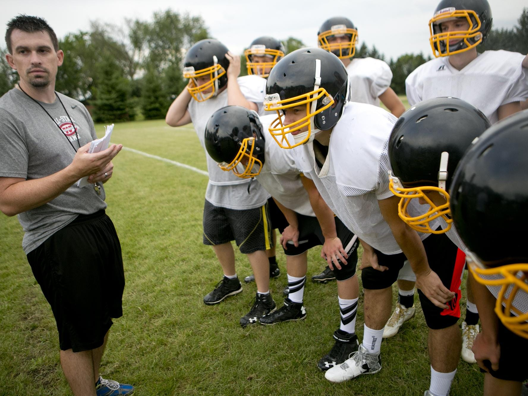Head coach Adam Spindler addresses the huddle before they run a play at Rosholt football practice, Aug. 6.