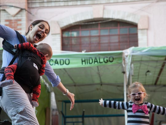 Shanna Hughey plays with her children, then-2-year-old Harper, right, and 6-month-old Walker, in the main market in Guanajuato, Mexico, in late summer 2013.