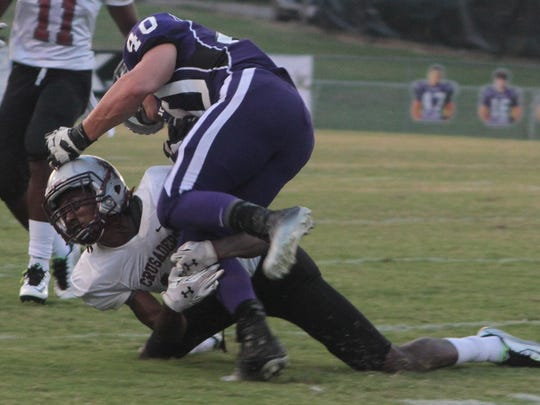 Liberty's Trae Dunlap (12) takes Milan's Tristen McDaniel (40) down low in the Crusaders' 30-8 win Friday.