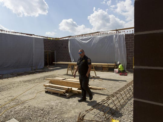 Tompkins County Correction Officer Robert Butcher walks through the expanded recreation area that is under construction at the Tompkins County Jail.