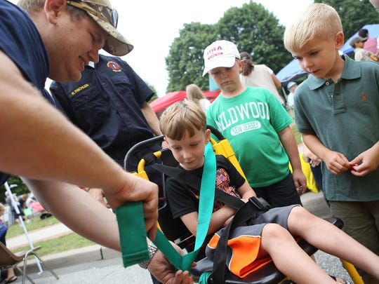 Bryan Kunze, a fireman and EMT with Roxbury Fire Department, buckles Drew Kraus, 4, of Hopatcong into a stair chair at the 28th annual Olde Suckasunny Day on Saturday. At right is Liam Connolly, 5, of Succasunna.