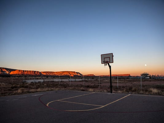 The moon rises over Thoreau in November 2014 as the sandstone mesa catches the last rays of sunlight and the Thoreau Community Center basketball court falls silent for the day.