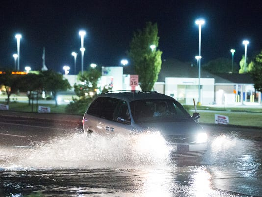 Cars drive through water being flushed from fire hydrants on Eisenhower Avenue on Saturday night, August 8, 2015.
