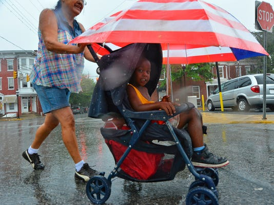 Mary Cievis pushes her grandson Elijah Kimmons, 3, across West King Street in York City during a downpour Thursday, Aug. 20, 2015.