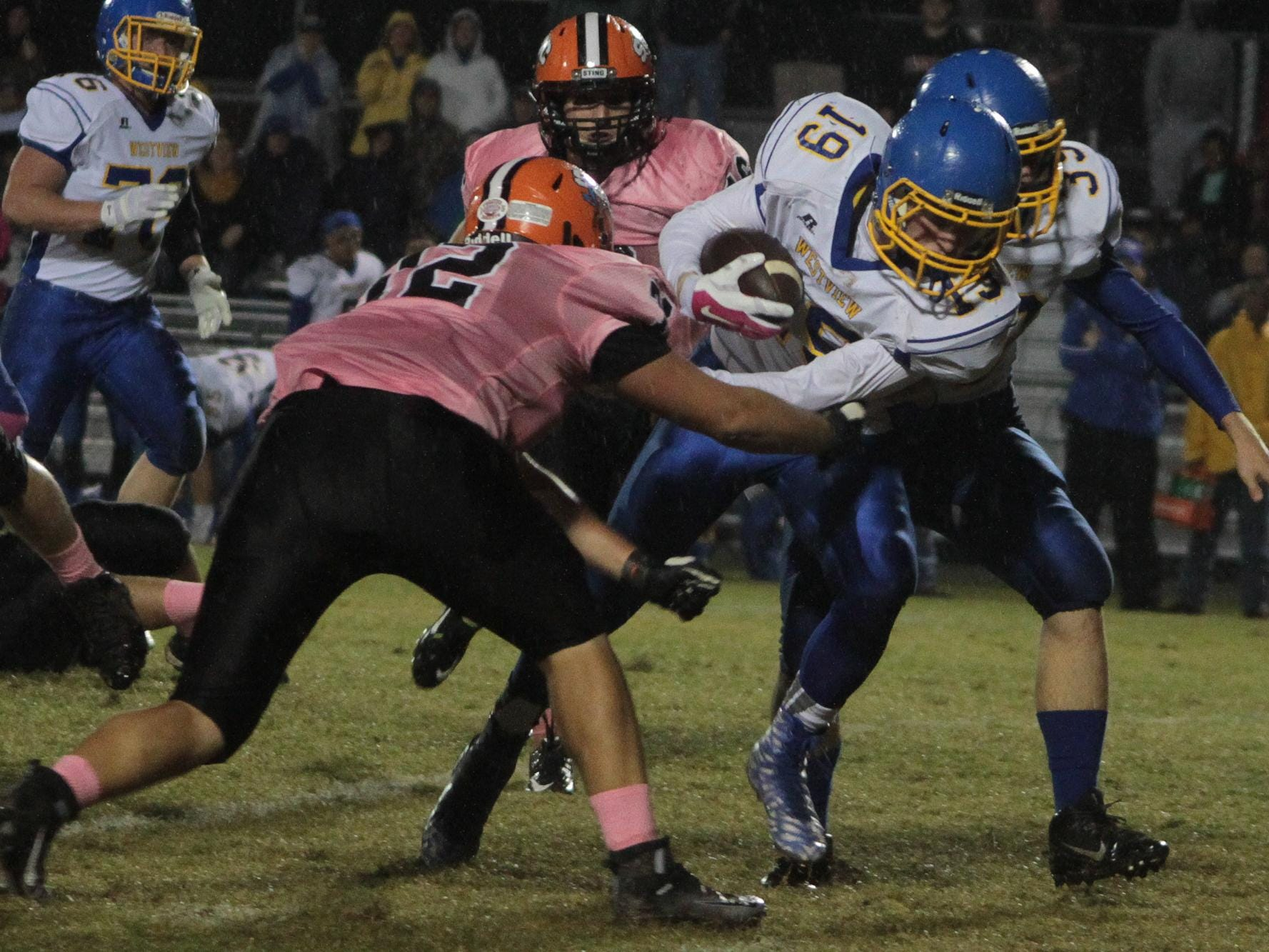 Westview's Parker Beal (19) pushes past South Gibson's Krayton Woods (72) to carry the ball a few more yards for the Chargers.