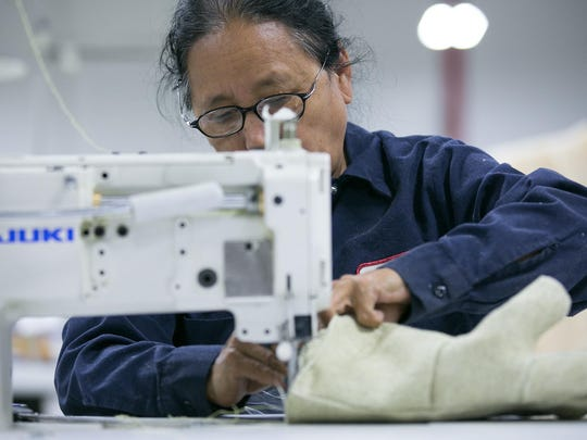 Tila Thapa of Henrietta sews at Newtex Industries in Victor on Wednesday, November 4, 2015.