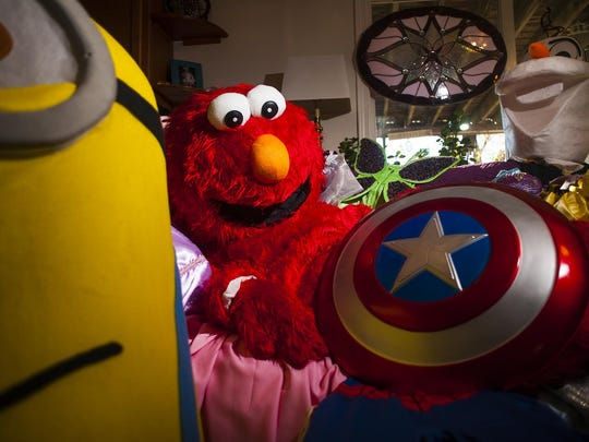 Whitney Graef, owner of Sweet Pea Princess Rental and More, poses in an Elmo outfit surrounded by other costumes including a Minion, Olaf, Captain America and many others. Graef and approximately 50 others are available for events around Great Falls.