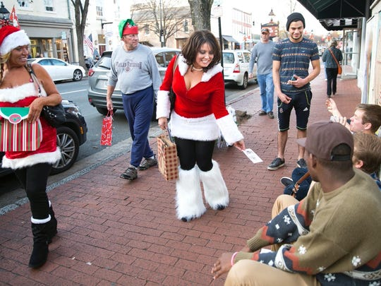 """Tiffany Neace celebrates her 40th birthday by handing out lottery tickets and toys in downtown Fredericksburg, Va., on Dec. 12. Because it was so much fun, she said, """"This is going to be my new birthday tradition."""""""