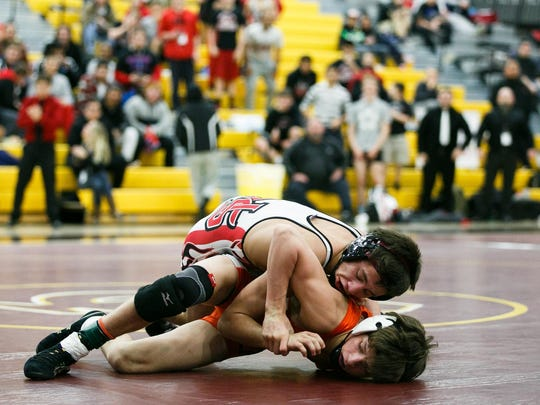North Salem's Brandon Quezada (white and red) wrestles Sprague's Daniel McClung (orange and white) at the Greater Valley Conference district wrestling tournament at Forest Grove High School on Saturday, Feb. 13, 2016. Quezada defeated McClung.