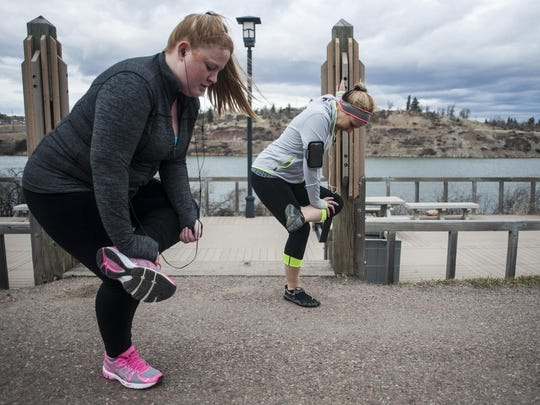 Emily Judkins, left, and Kathy Milling, stretch before a run along River's Edge Trail. Regular exercise while still maintaining social distancing can help fight depression and anxiety during the coronavirus pandemic.