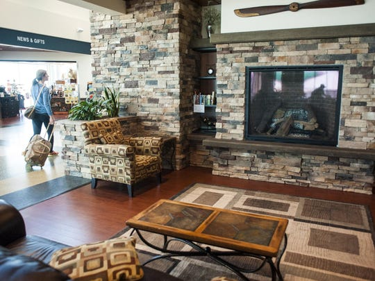 A traveler walks through a lobby and fireplace sitting area behind security at Great Falls International Airport.