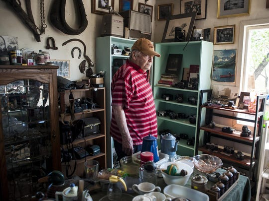 Ed Bischoff stands in his shop, Little Missouri Gallery, filled with antiques and oddities he has found over the years. His collection includes everything from antique cameras to ranching equipment.