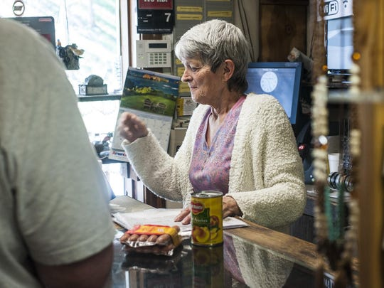 """Nancy Kingsbury helps a customer at a convenience store in Sula. The place is for sale """"because I'm old,"""" she said. """"I've been here 19 years and it's time to move on. If I wasn't younger, I wouldn't even think of selling."""""""