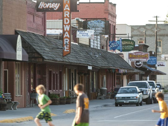 Children jog across the street lined with buildings whose signs evoke the past.