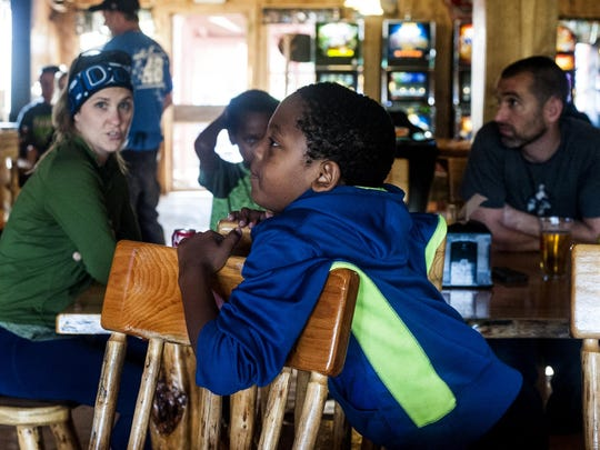 Nurson Schmidt, an 8-year-old adopted from Ethiopia, watches the game with his family at the Yaak River Tavern.