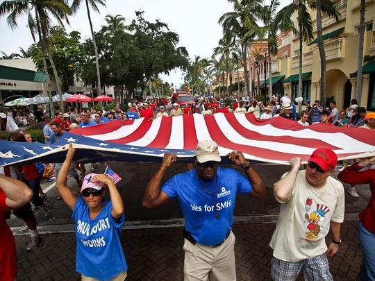 In this 2012 file photo, St. Matthew's House representatives carry a large American flag during the annual Fourth of July parade in downtown Naples on Wednesday, July 4, 2012. William DeShazer/Staff