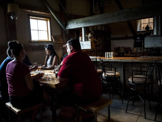 Patrons sit around a table near the bar at Wildwood Brewing in Stevensville.