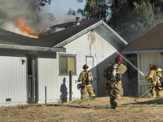 Visalia and Tulare County Fire Departments work a 2-alarm fire involving two homes and threatening others in the 2600 block of South Kloth Drive on Friday, July 15, 2016. Initial estimate for total damage was $250,000. No injuries were reported. The fire was first reported at 5:13 p.m. and eventually brought seven engines and one ladder truck.