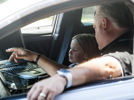 Julianna Graef, 8, listens to Sgt. Jim Wells explain laptop functions in a police car after reading a letter and delivering cookies to show her respect at the Great Falls Police Department on Wednesday.