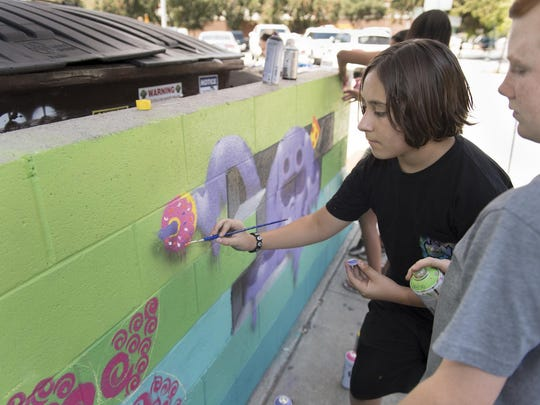 "Jackson Ford, right, Emilio Gonzalez and other students from Arts Visalia's annual summer art class program put the finishing touches on ""Color Fusion"" on Friday, July 22, 2016. Their canvas, a trash enclosure in Downtown Visalia, is part of a project with UrbanArtWorks and the Urbanist Collective that includes four other enclosures with hopes to add more."